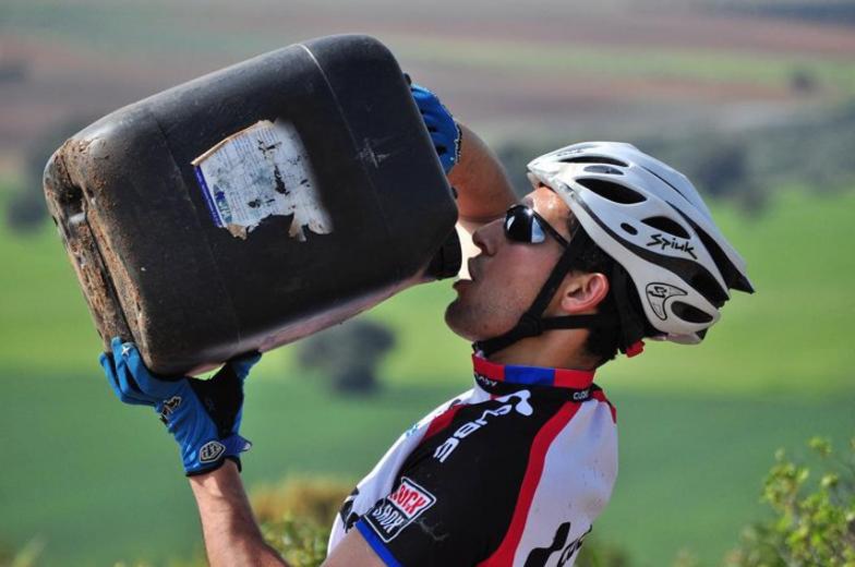 Велосипедист пьет воду во время путешествия