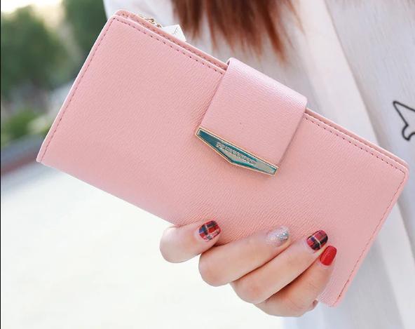 Большой женский кошелек в руках девушки