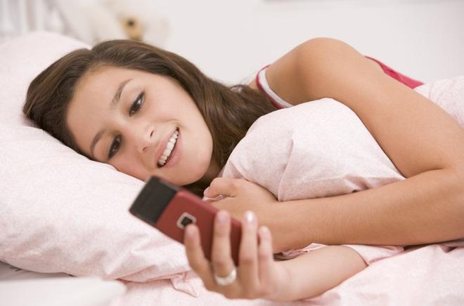 Дівчина в ліжку з телефоном
