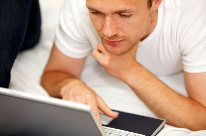 Хлопець читає повідомлення в ноутбуці