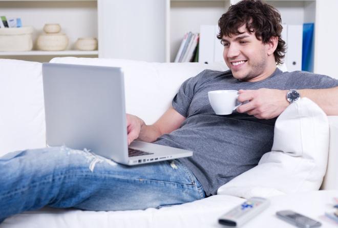 Хлопець посміхається читаючи ноутбук