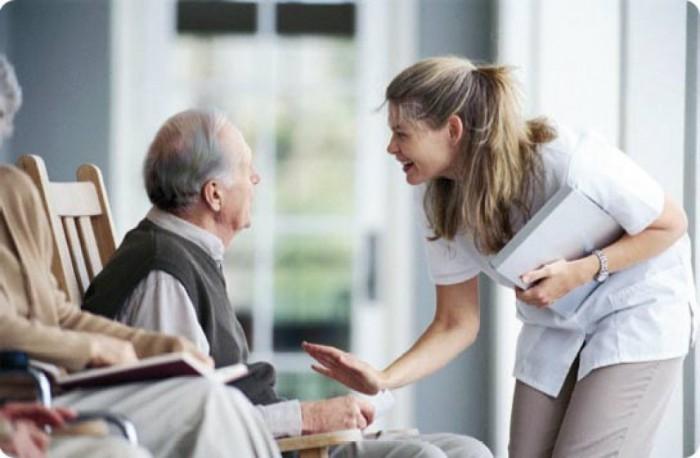 Медсестра ухаживает за дедушкой в доме престарелых