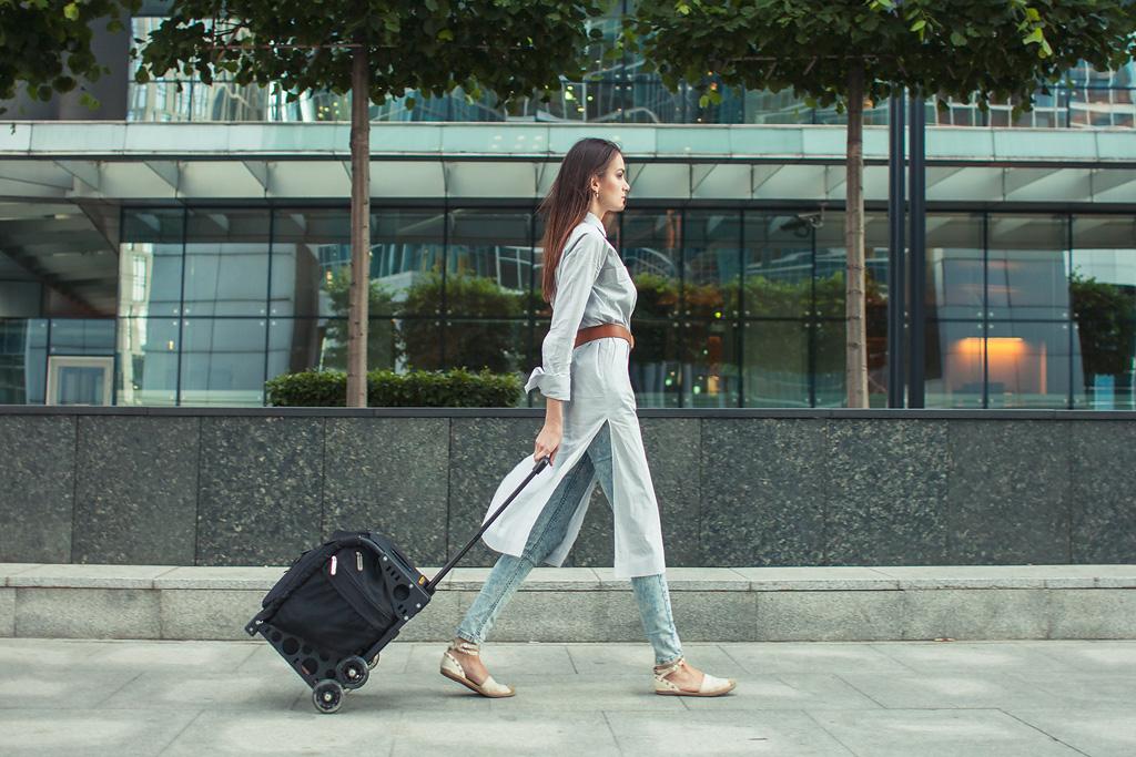 Дівчина з сумкою на коліщатках гуляє містом